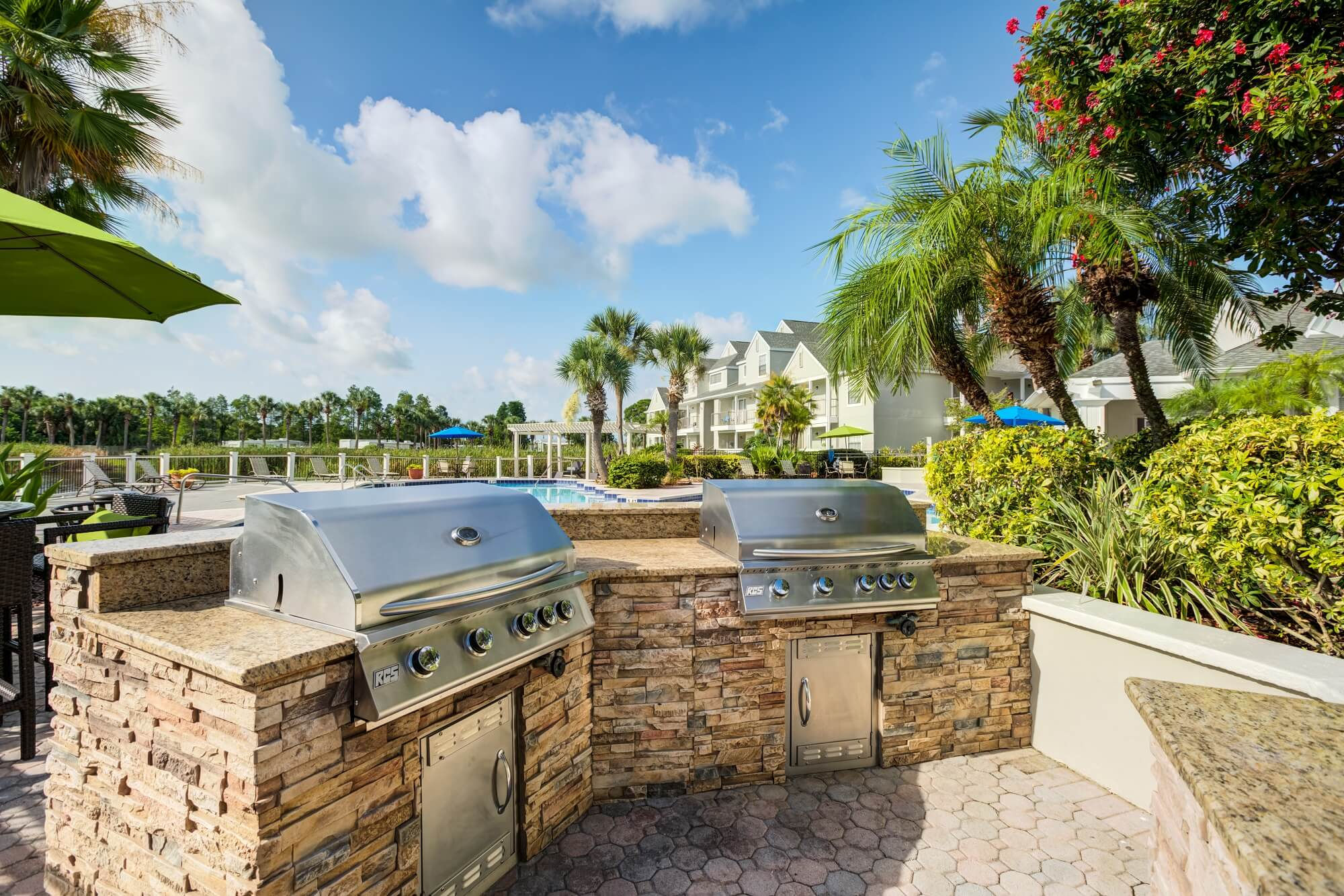 two 4 burner grills with stone countertops near the pool.