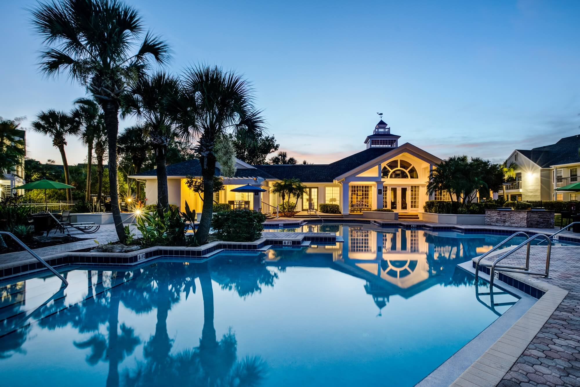 night time pool view with palm trees, lounge chairs, and view of clubhouse.