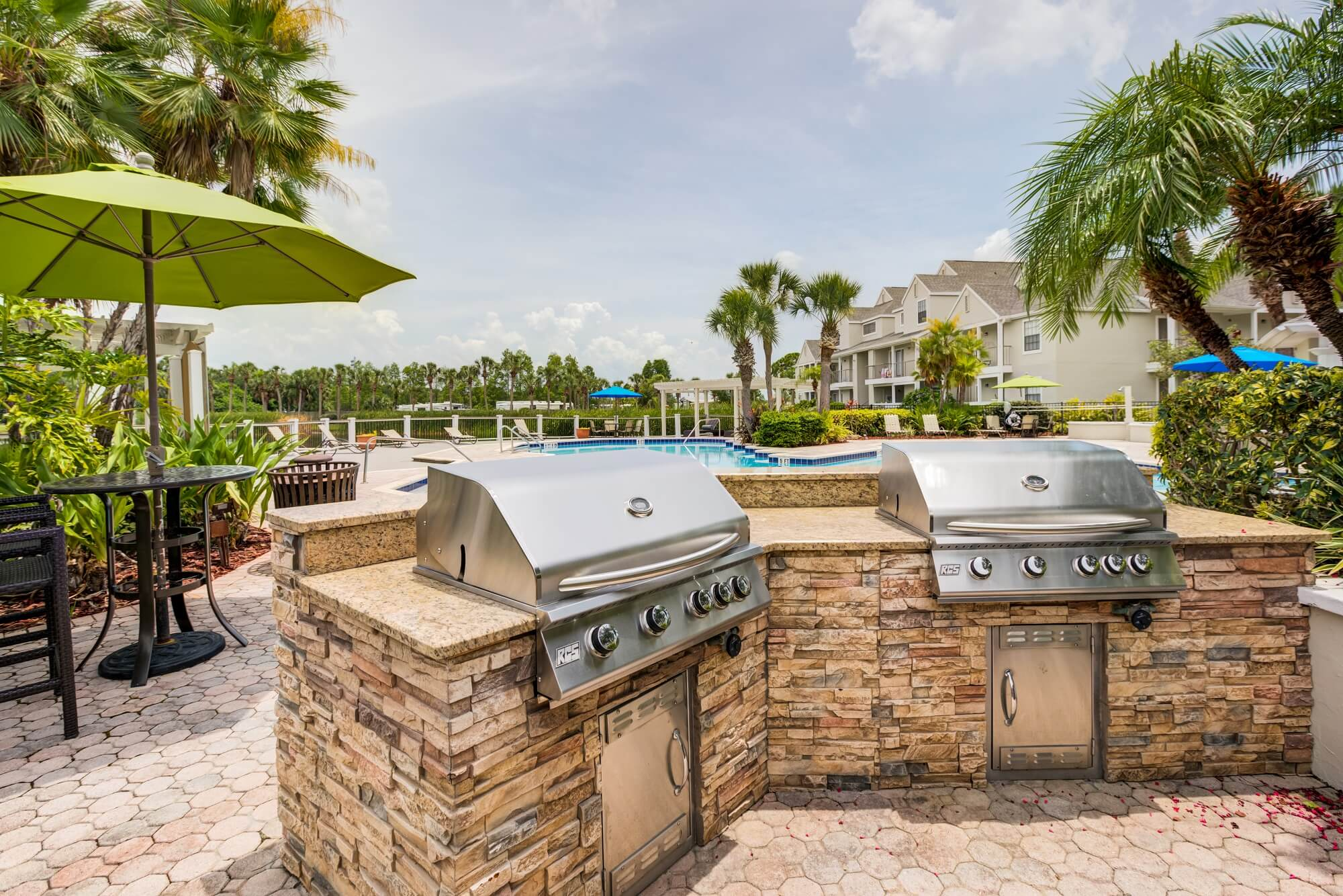 two 4 burner grills with stone countertops with view of the pool.