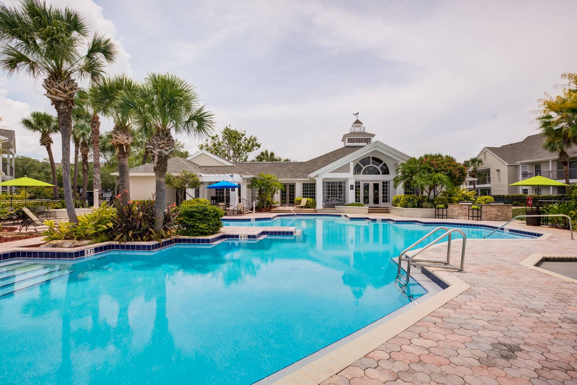 large pool view with palm trees and view of the clubhouse.