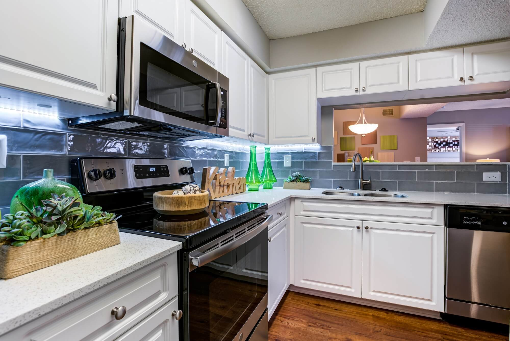 l-shaped kitchen with white cabinets, tiled backsplash, stove, microwave, and dishwasher.