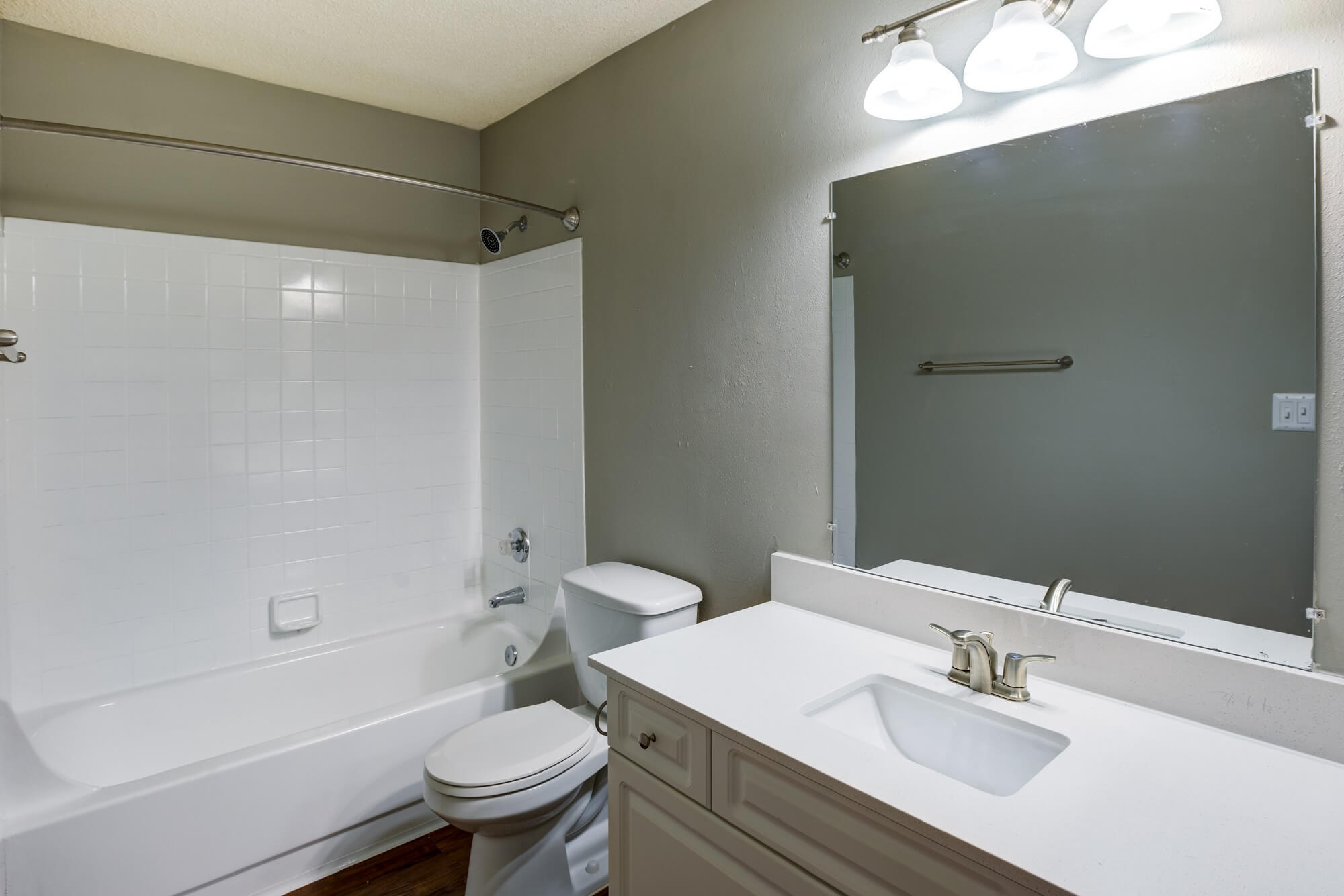 bathroom with single sink, mirror, overhead lighting, toilet, and tub.