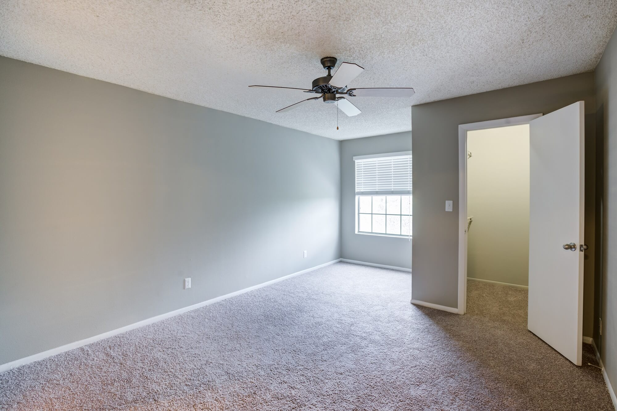 unfurnished bedroom with carpet, ceiling fan, and small closet.